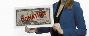 Woman holding $50 bill with donate written on it